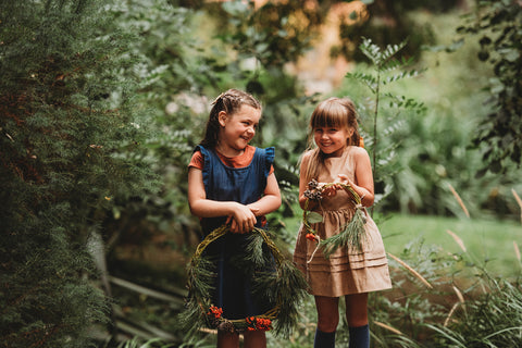 Wild Books two girls in forest with Christmas Wreaths handmade