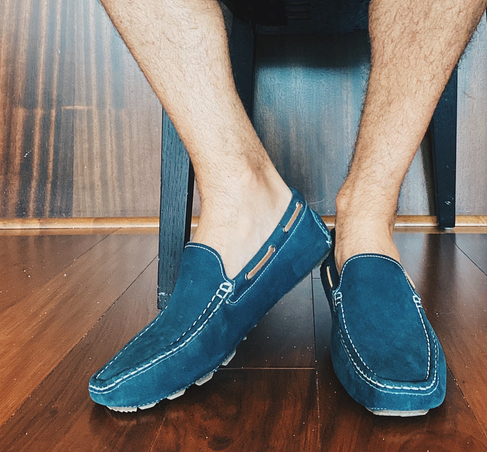 Photo of man's legs and feet wearing loafers, with socks not visible