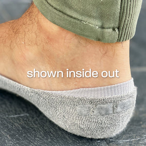 Photo showing close-up of Skinnys sock heel-cup inside out on a man's foot, revealing padding and wrap-around gel grip