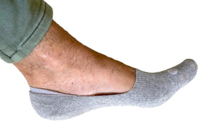 Photograph of a Skinnys padded-heel sock on a man's foot from the side, on a white studio background, revealing low-cut nature of sock