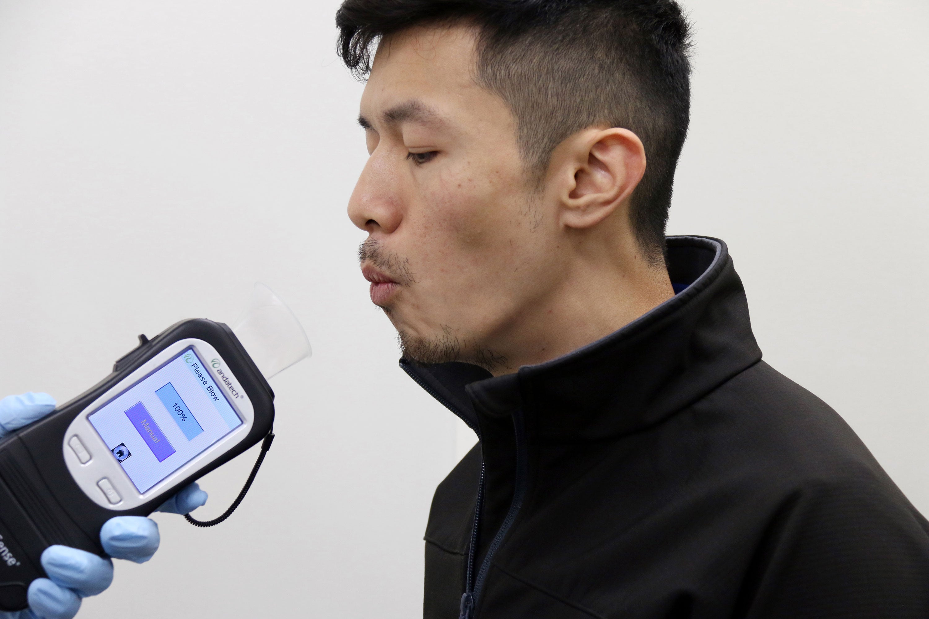 Man blowing into an Andatech Prodigy 2 Breathalyzer