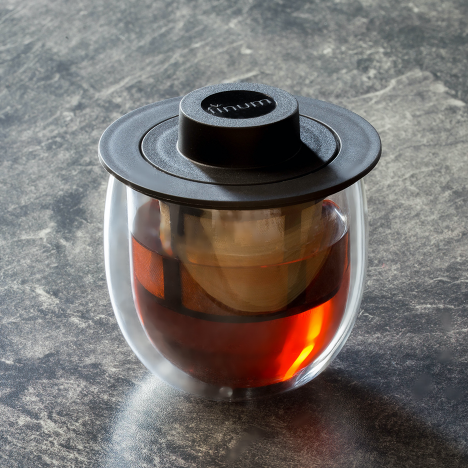 Finum Double Walled Glass with reusable stainless steel filter and a black-colored lid.