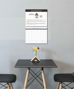 Calendar hanging on a simple wall above a table with two chairs and a vase of flowers