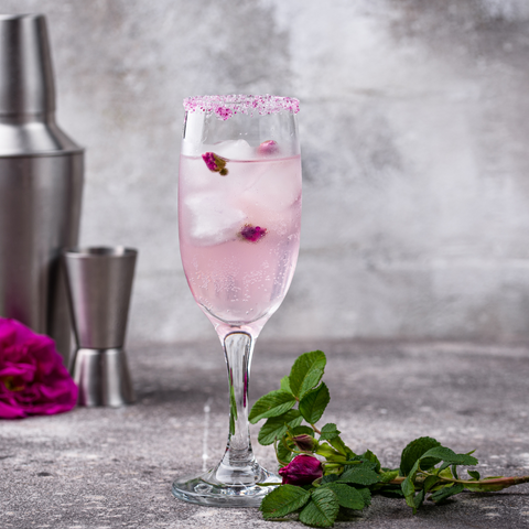 Rose Martini, shown in a champagne flute, with pink edible rose petals
