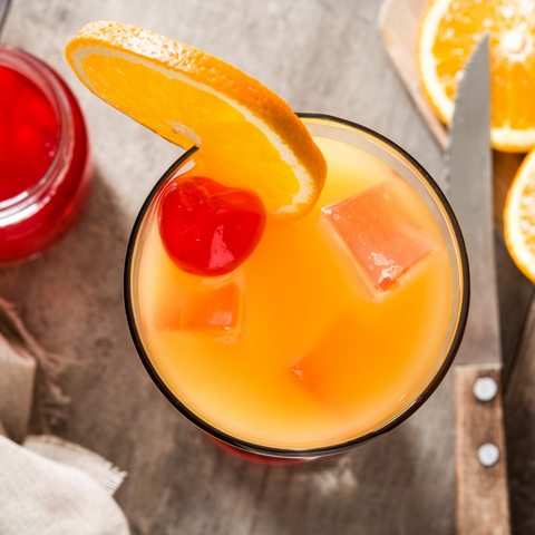 A Tequila Sunrise topped with freshly sliced oranges and maraschino cherries
