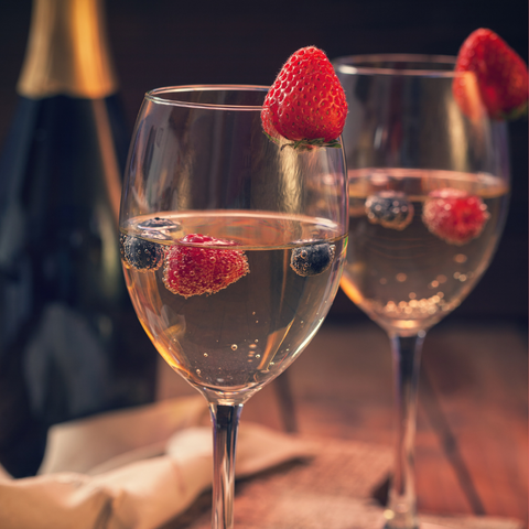 Glasses with Champagne, a touch of hibiscus syrup and strawberry purée with fresh berries