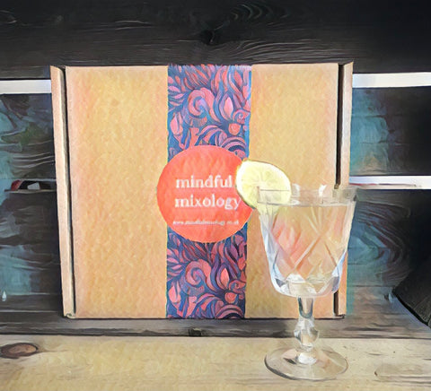 A sketch of the Mindful Mixology gift box, with brightly coloured packaging- on a dark wooden crate. Shown in front is a chilled glass of the lychee martini