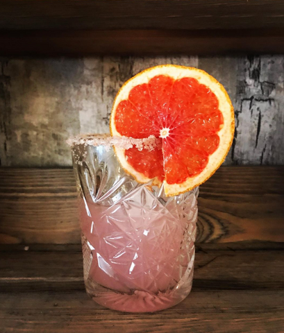 Mindful Mixology's pink grapefruit margarita, in a short crystal tumbler. Pink salt is on the rim, and a thin grapefruit wheel decorates the glass.