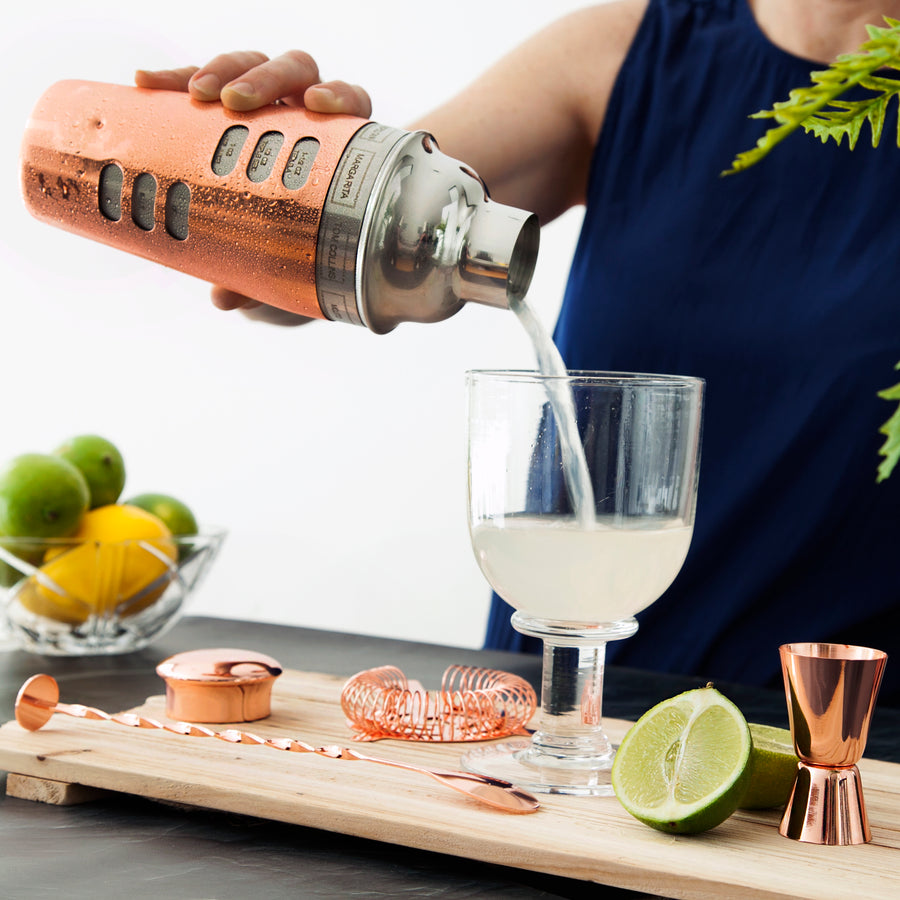 A women is shown in the background pouring a gimlet from a copper cocktail shaker into a short chilled cocktail glass. The cocktail is opaque in colour and is surrounded by freshly cut limes and lemons.