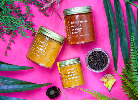 A smaller image of jars of spices made by Diaspora Co against a pink background. One small jar of turmeric, one small open jar of peppercorns, one large jar of turmeric, and one large jar of Sannam chiles.