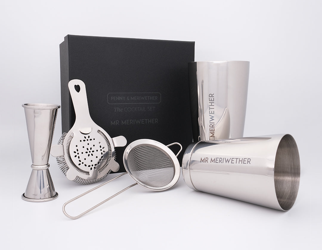 A cocktail gift set including personalised shaker tins, a fine strainer, a Hawthorne strainer, jigger and personalised gift box