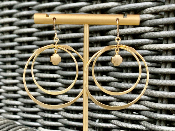 Gold double hoop earrings with cross accent.
