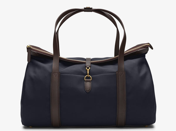 Measurements: L: 52 H: 29 W: 18 (27) cm Body: Hard-woven waterproof nylon Fabric composition: PA 42% CO 38% PU 20% - 826 g/m Trimmings: Dark brown custom developed vegetable tanned full-grain bridle leather Lining: 100% cotton in navy colour Hardware: Solid brass with varnish protection Zipper: Hand polished YKK Excella The refined little brother of M/S Explorer boasts the same DNA but with a different shape and detailing. The Adventurer is a carry-on ideal for weekend trips