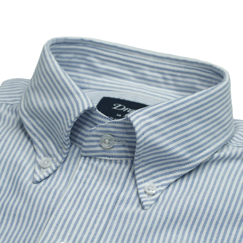 Slim fit shirt with ticking blue stripes and button-down collar. Classic and very versatile shirt for casual dressed up days. You can wear it with a tie but it sure is at it's best without one.  A stable for every mans wardrobe.   100% Cotton. Handcrafted in Somerset, UK.  Slim Fit Button-down collar with soft feel Box pleat Single round one button cuff Point pocket Mother of Pearl buttons 100% cotton Made in England