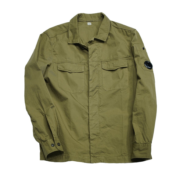 C.P. Comapany overshirt made of 100% cotton gabardine. This version is quite true to the authentic military field shirts. The fit is quite straight and sleeves are cuffed. Button fastening in front and 2 flap chest pockets in front. Small pocket on left sleeve with embedded C.P. Lens.  100% Cotton gabardine 2 flap pockets pocket on lefty sleeve with a C.P. Lens  08CMSH292A 005383G Col. 660