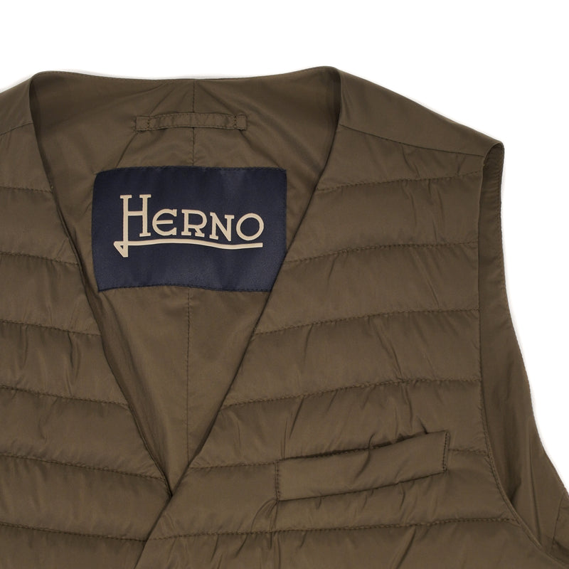 Herno In-Tech™ Alternative Down Waistcoat in Green. Great piece for layering.A true must have for every modern gentleman.  Wear it under jacket or over a knit. Great for traveling as it packs small and weighs almost nothing.   In-Tech™ Alternative Down Water Repellent  Breathable Light Insulation 5 buttons  3 pockets  Adjustable back External layer 100% Polyamide Internal padding 100% Polyester  PC0039U 19288 7745 Made in Romania