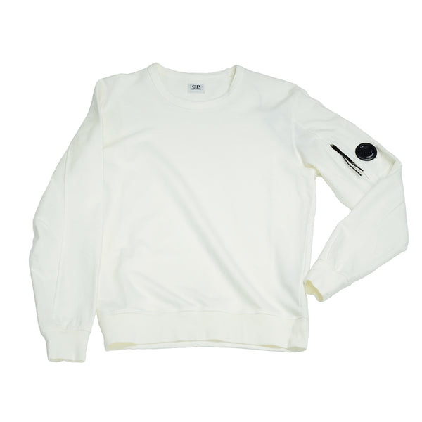 C.P. Company Garment Dyed Light Fleece. Pocket with a  C.P. Lens detailing and a zip on the left sleeve.   Garment dyed Crewneck construction Long sleeve Ribbed cuffs and hem Lens detail in sleeve pocket 100% cotton Fits true to the size 08CMSS053A 002246G Col. 100