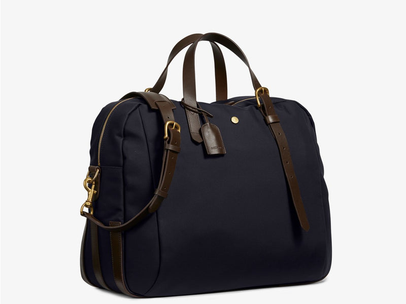 Measurements:   L: 47  H: 42  W: 31 (12) cm Body: Waterproof hard woven Italian nylon  Fabric composition: PA 42%  CO 38%  PU 20%   /   826 g/m Trimmings: Dark brown custom developed vegetable tanned full-grain bridle leather Lining: 100% cotton in navy colour  Hardware: Solid brass with varnish protection  Zipper: Hand polished YKK Excella The perfect holdall for the active lifestyle. The M/S Something easily does the job for any trip