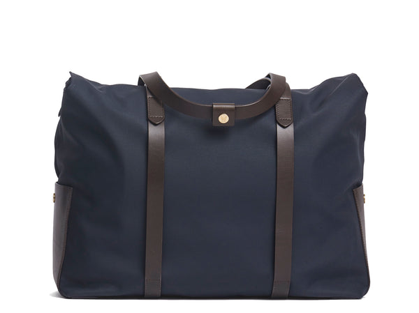 Measurements:  L: 46  H: 34  W:18 cm Body: Waterproof hard woven Italian nylon  Fabric Composition: PA 42% CO 38% PU 20%  /  826g pr. meter  Trimmings: Dark brown vegetable tanned full-grain bridle leather   Lining: 100% cotton in Navy colour Hardware: Solid brass with varnish protection  Zipper: Hand polished YKK Excella Art. No. MS111312 travel bag, or bend flaps down for a large, open city tote bag.  A full-grain leather pocket on each gusset adds extra durability to the bottom corners