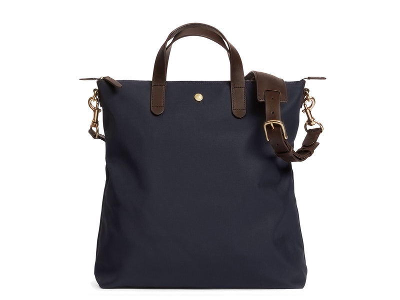 Measurements:  L: 37 x H: 41 x W: 10 cm Fabric composition: PA 42% CO 38% PU 20%  /  826g pr. meter  Body: Waterproof hard woven Italian nylon Trimmings:  Custom developed dark brown vegetable tanned full-grain bridle leather Lining: 100% cotton in navy colour Hardware: Solid brass with varnish protection  Zipper: Hand polished YKK Excella Art. No. MS251312 As the first style ever launched in the Contemporary collection, the M/S Shopper has grown to become one of the most iconic styles of the Mismo
