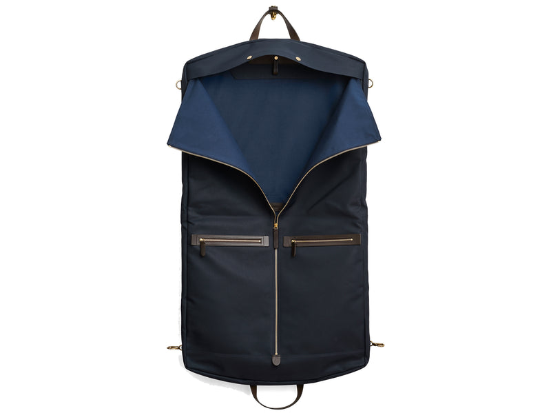 Measurements: L: 52 x W: 50 x H: 7 cm Body: Waterproof hard woven Italian nylon Fabric composition: PA 42% CO 38% PU 20% / 826g /m Trimmings: Dark brown custom developed vegetable tanned full-grain bridle leather Lining: 100% cotton in navy colour Hardware: Solid brass with varnish protection Zipper: Hand polished YKK Excella Art. No. MS441315 Transporting your work, wedding, and/or weekend wear just got a whole lot easier. Slip garments into first ever full size garment bag large to carry all mismo