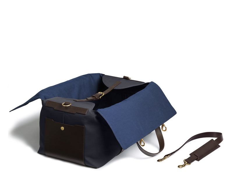 Measurements: L: 52 H: 25 W: 28(26) cm Body: Waterproof hard woven Italian nylon Fabric composition: PA 42% CO 38% PU 20% / 826g/m Trimmings: Dark brown custom developed vegetable tanned full-grain bridle leather Lining: 100% cotton in navy colour Hardware: Solid brass with varnish protection Zipper: Hand polished YKK Excella Art. No. MS411315 Travel, gym, tennis life's adventures take the M/S Supply is a great addition. Elongated handles easy to carry bag by hand, hung over shoulder worn rucksack