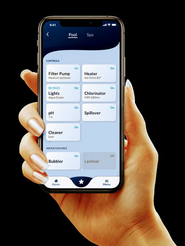 Womans hand holding smartphone with Omnilogic app shown. Easy control of all your swimming pool equipment.