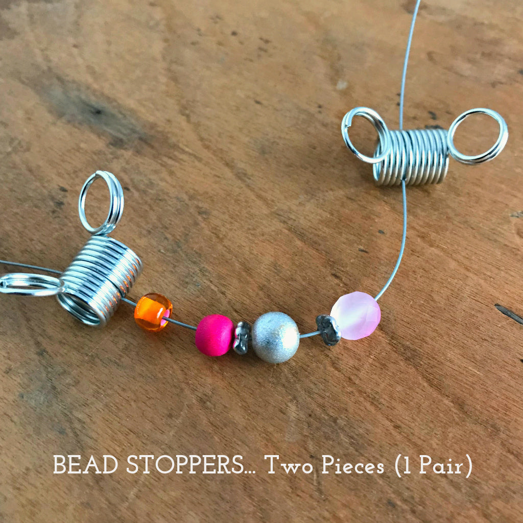 "Suzie Q Studio's ""must have"" bead stringing invention, the Bead Stopper, prevents the beads on your bead stringing wire from slipping off the end while you create your design. They're super-easy to use… Simply squeeze the rings to open the coils, slide in your bead stringing wire, release the rings and you're ready."