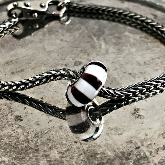 Suzie Q Studio has a treasure vault full of Rare & Retired Trollbeads. The elegant, wide and dramatic black and white zebra stripes of this Black and White Stripes Rare & Retired Trollbead ensures that it will go well with other Trollbeads.