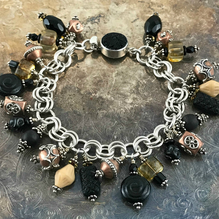 Available at Suzie Q Studio -- Czech glass, copper, sterling bead charm bracelet. The neutral colored bead-charms featured on this handcrafted sterling silver charm bracelet will go with a wide variety of styles and colors of outfits in your wardrobe.