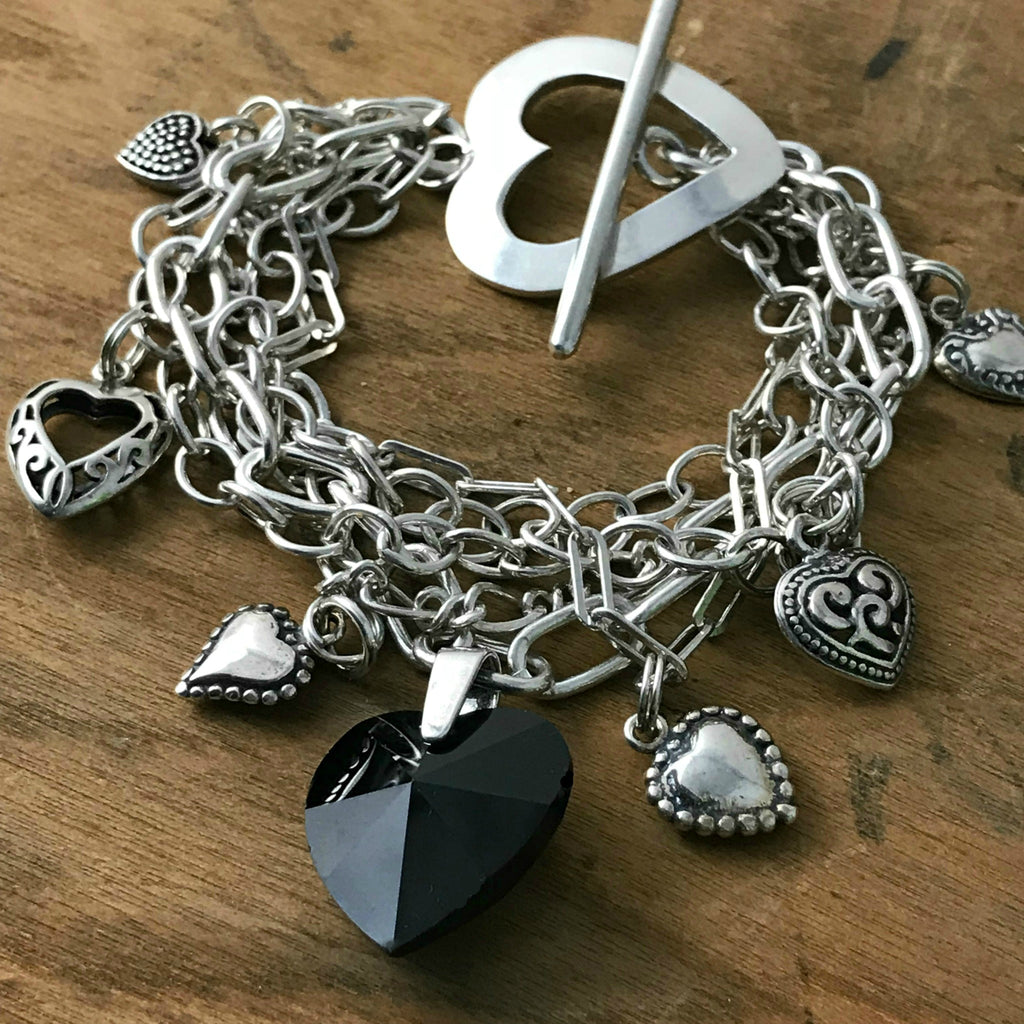 Suzie Q Studio -- Multi-strand sterling silver chain and charm bracelet. This sterling silver, multi-strand charm bracelet has a black Swarovski crystal heart focal charm, combined with sterling silver chain, charms and spectacular sterling silver, heart-shaped toggle-style clasp.