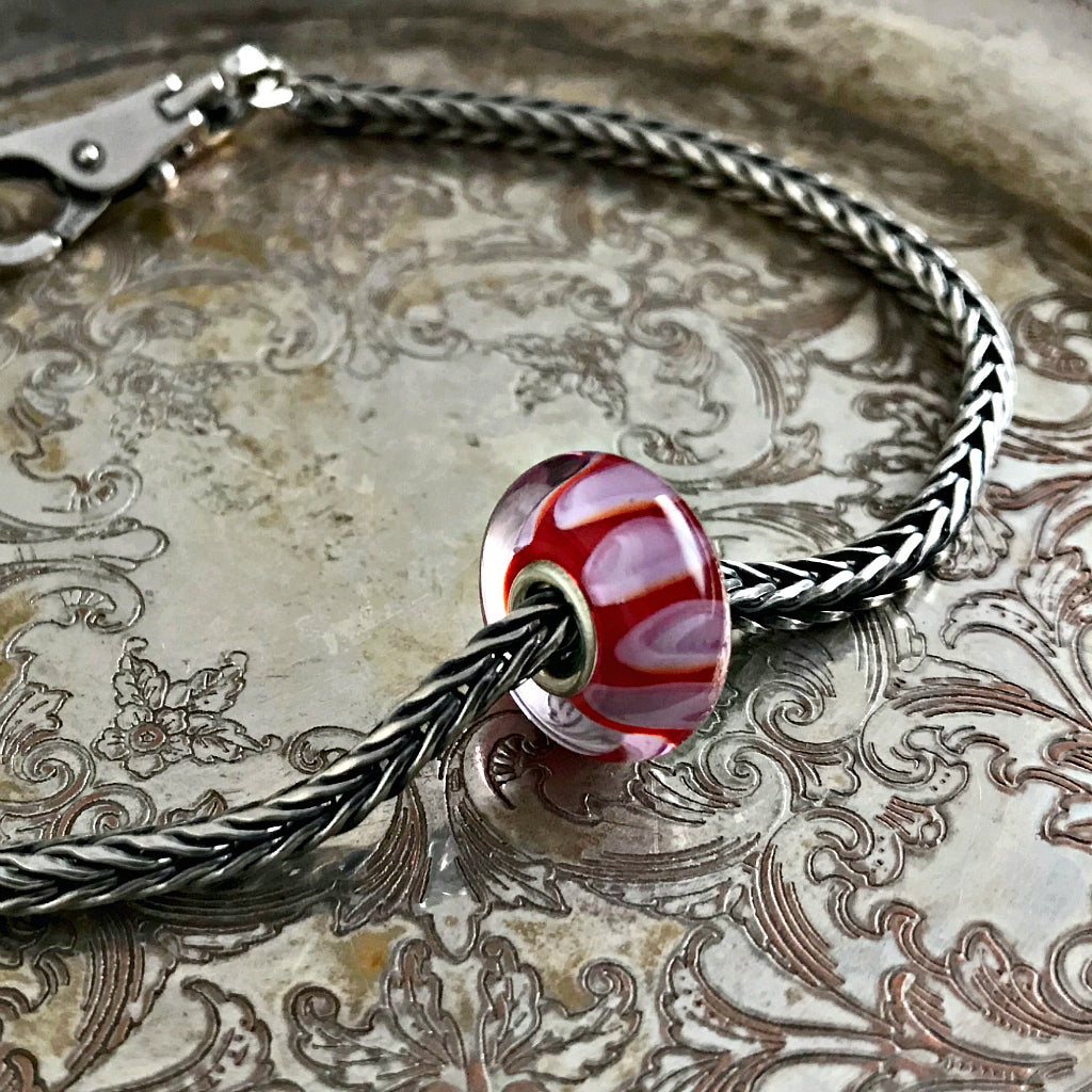 Suzie Q Studio has a treasure vault full of Rare & Retired Trollbeads... and we're making them available to you. We're starting with our Rare & Retired Glass Beads. This rare Trollbead is an optical illusion in red and lilac.