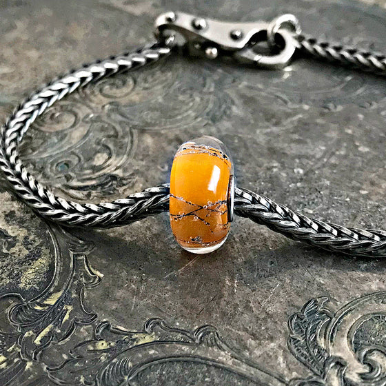 Suzie Q Studio has a treasure vault full of Rare & Retired Trollbeads... and we're making them available to you. We're starting with our Rare & Retired Glass Beads. Orange golden glass engulfing threads of steel in an exciting and very different Trollbead.