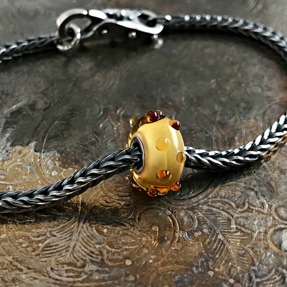 Suzie Q Studio has a treasure vault full of Rare & Retired Trollbeads... and we're making them available to you. We're starting with our Rare & Retired Glass Beads. Glass allows you to play with colors like no other material. This retired Trollbead is a combination of dark and light brown that looks like yummy honey and maple syrup!