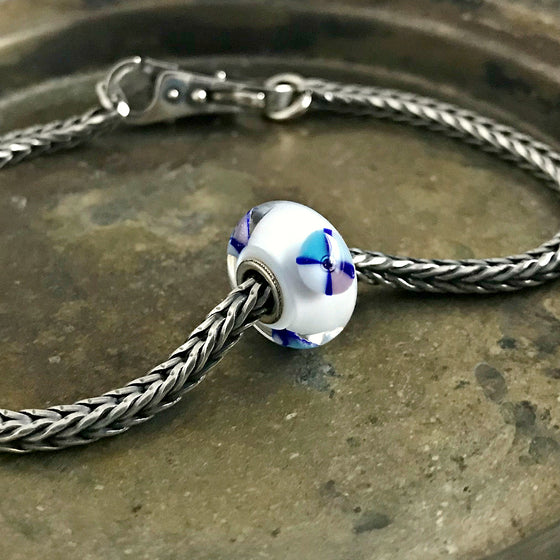 Suzie Q Studio has a treasure vault full of Rare & Retired Trollbeads... and we're making them available to you. We're starting with our Rare & Retired Glass Beads. The whimsical wheels of pastel tones in this retired Trollbead spin around on a bed of snowy white glass… Lots of depth with this beauty.