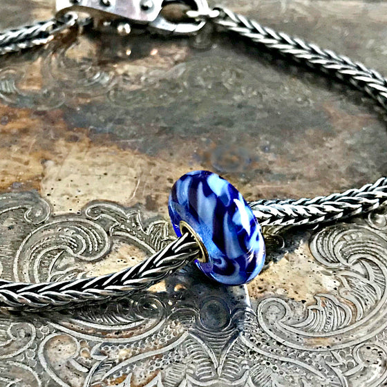 Suzie Q Studio has a treasure vault full of Rare & Retired Trollbeads... and we're making them available to you. We're starting with our Rare & Retired Glass Beads. Dark and light-blue braids come together into a joyful ribbon in this rare Trollbead.