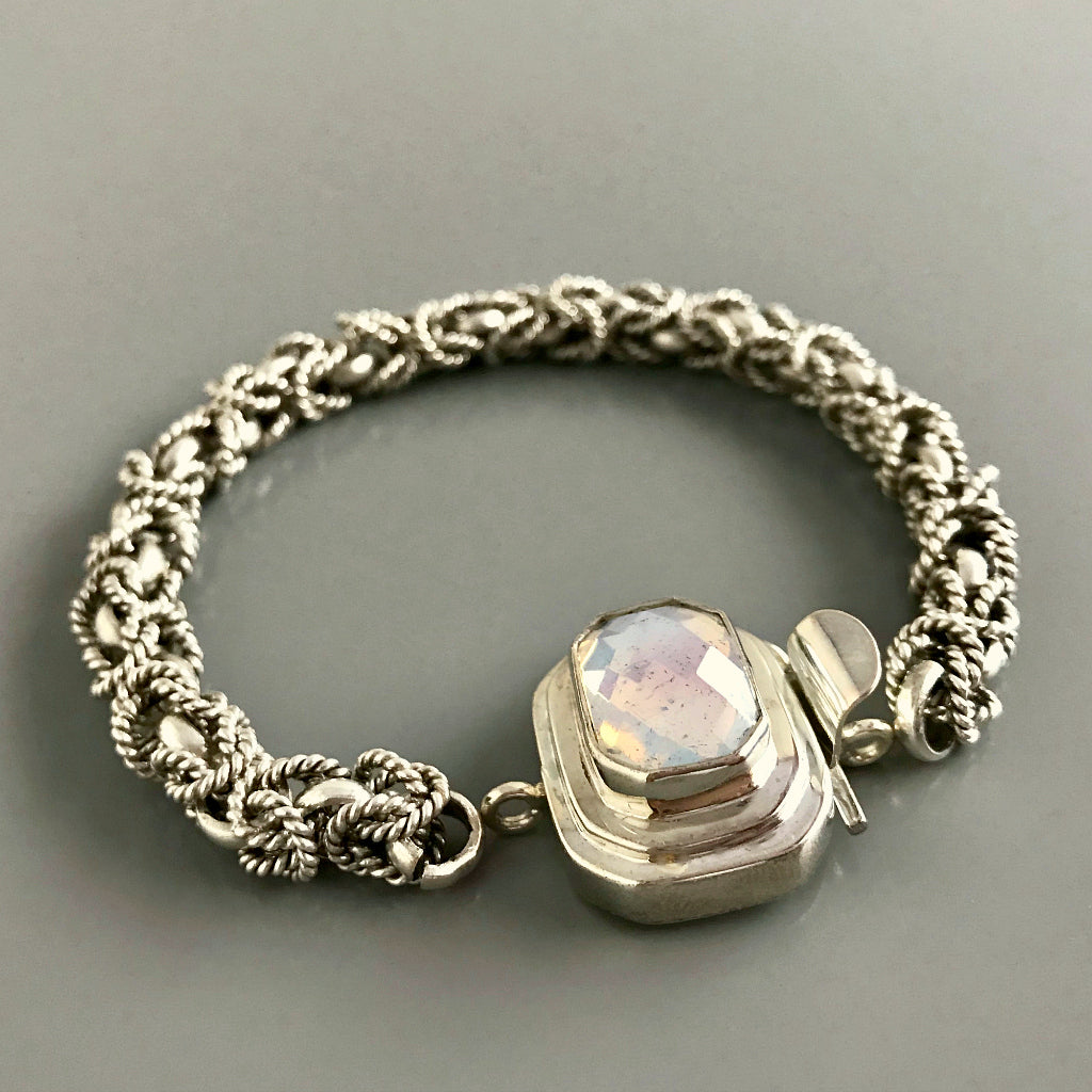 This Suzie Q Studio custom box clasp was handcrafted with a rectangular, white opalescent, vintage glass cabochon and set in sterling silver. The finish of the glass piece used in this closure is distressed, and along with the faceting and cut corners of the rectangle shape, contributes to its beautiful antique feel.