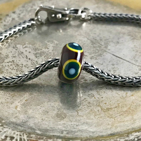 "Suzie Q Studio has a treasure vault full of Rare & Retired Trollbeads... and we're making them available to you. The inspiration for the GREEN EYE BEAD comes from an old Middle-Eastern tradition, where eyes like these are believed to protect against ""evil eyes"" and bring good luck to their owner."