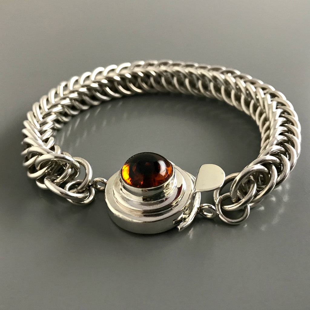 This Suzie Q Studio custom box clasp was handcrafted with a round, amber-style, vintage glass cabochon and set in sterling silver. The swirl of dark brown in the centre of a pool of maple syrup coloured glass gives this box clasp a decided look of real amber!