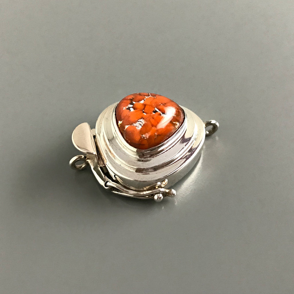 "This Suzie Q Studio sterling silver custom box clasp is a very unusual and distinctive closure. The triangle shape of this vintage glass cabochon coupled with the mottled, burnt orange color on a base of silver ""leaf"", showcases a retro-1950's feel as well!"