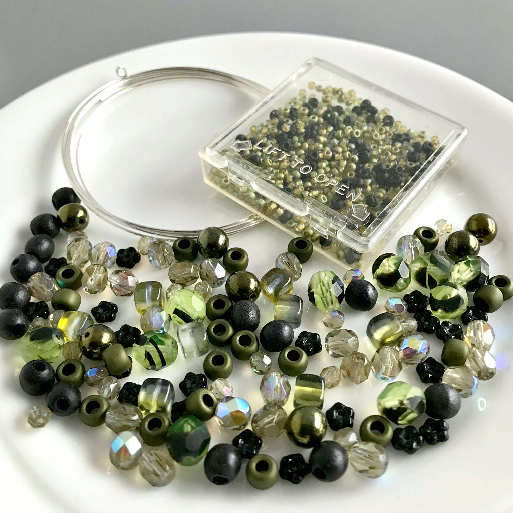"Suzie Q Studio's Serendipity BEAD STEW DIY EASY BANGLE STYLE BRACELET MAKING KITS are limited edition collections of artfully curated premium quality beads and components for you to make a one-of-a-kind bracelet that'll have the look of multiple bangles stacked on your wrist. No experience needed!  With the subtle hint of warm-hued ""basil"" greens, along with the classic black of ""poppy seeds"", the BASIL POPPY SEED DRESSING bracelet kit is perfect for someone who enjoys a more understated, delicate look."