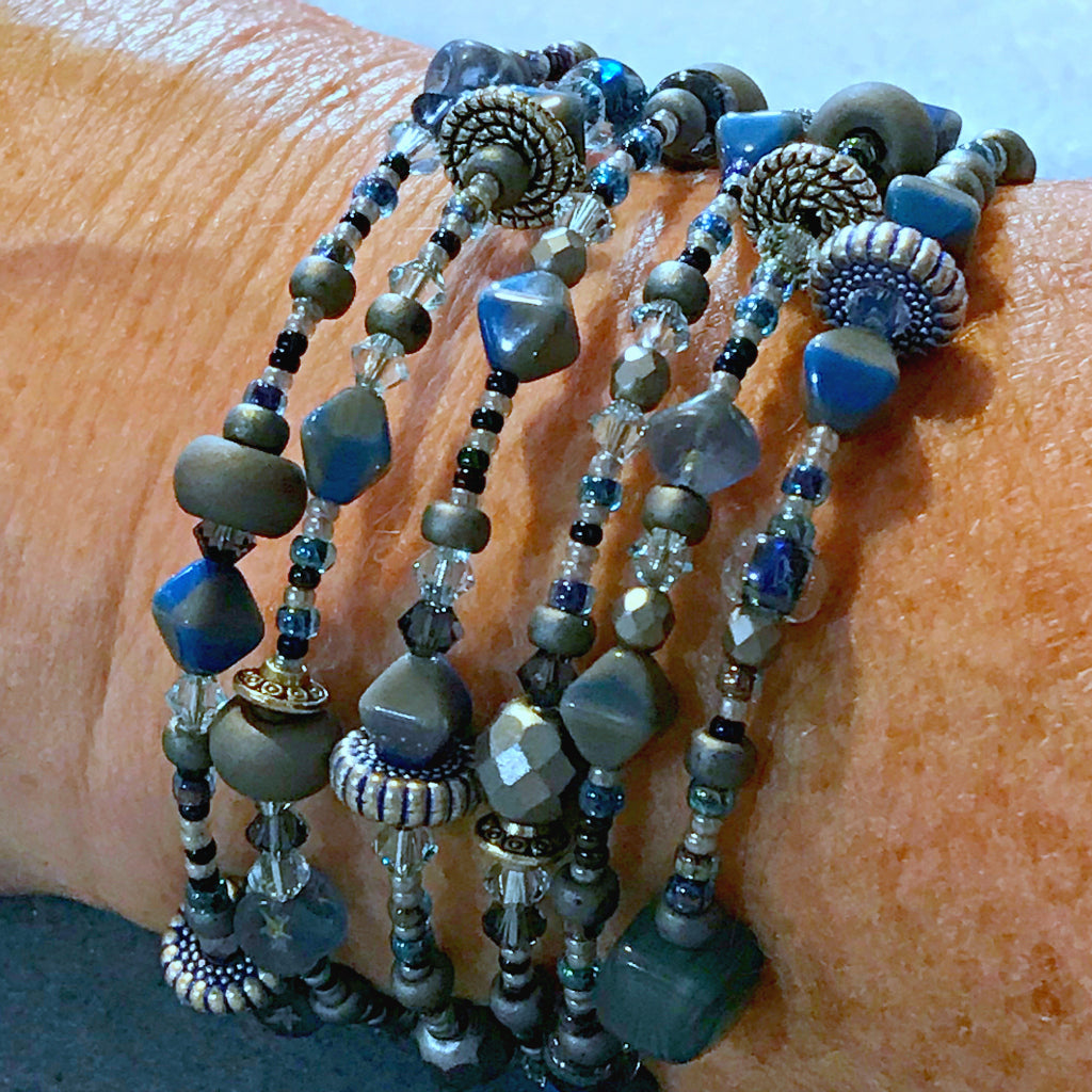 "Suzie Q Studio's Serendipity BEAD STEW DIY EASY BANGLE STYLE BRACELET MAKING KITS are limited edition collections of artfully curated premium quality beads and components for you to make a one-of-a-kind bracelet that'll have that super-cool look of multiple bangles stacked on your wrist. No experience needed!  ""Cookie Monster"" kit contains various shades of blues, including ""Cookie Monster"" blue, grey, metallic blue-grey, metallic silver."