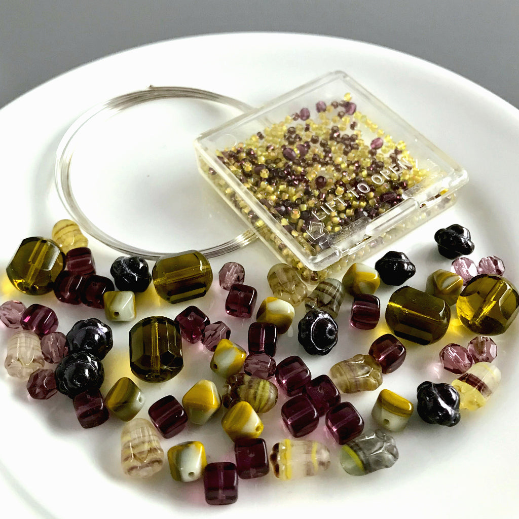 "Suzie Q Studio's Serendipity BEAD STEW DIY EASY BANGLE STYLE BRACELET MAKING KITS are limited edition collections of artfully curated premium quality beads and components for you to make a one-of-a-kind bracelet that'll have that super-cool look of multiple bangles stacked on your wrist. No experience needed! The ""Wine & Avocado Toast"" Kit contains various shades and tones of yellow-green, such as ""olive"" and ""avocado"", warm grey and amethyst-purples, metallic eggplant and a hint of metallic silver."