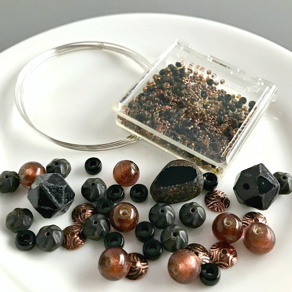 "Suzie Q Studio's Serendipity BEAD STEW DIY EASY BANGLE STYLE BRACELET MAKING KITS are limited edition collections of artfully curated premium quality beads and components for you to make a one-of-a-kind bracelet that'll have that super-cool look of multiple bangles stacked on your wrist. No experience needed!  This ""Black Velvet Apricot"" kit contains matte and shiny black, sparkly bronze-copper and metallic, antique copper beads."