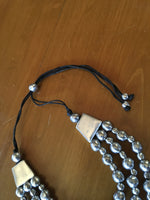 Adjustable aluminum three thread necklace with balls.