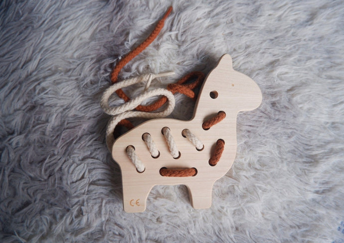 Wooden crafted llama lacing toy with three threads of different colours.