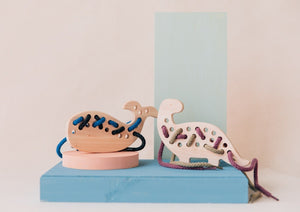 Wooden crafted whale and dinosaur lacing toys with threads of different colours.