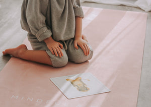 A child practicing yoga on a kids yoga mat with yoga flash card.