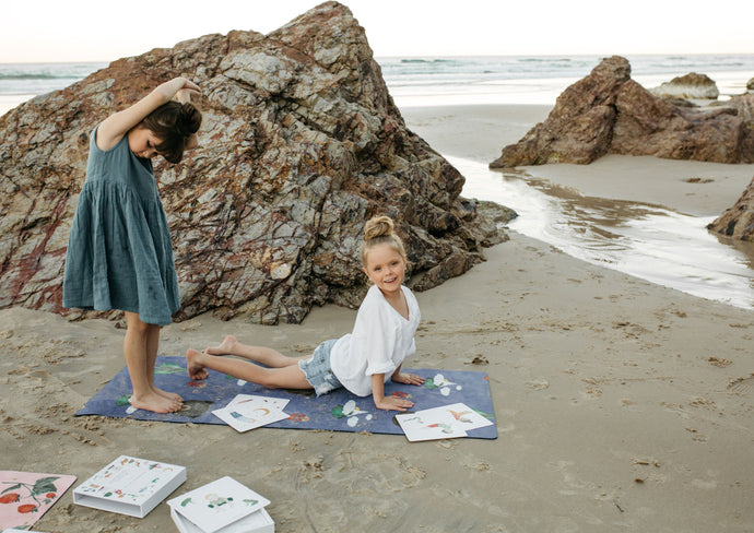 Girls practicing yoga on a yoga mat, on a beach.