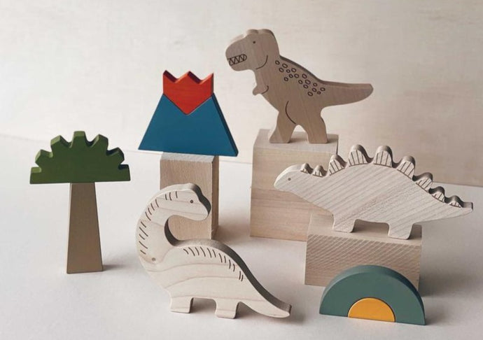 Wooden crafted Stegosaurus, Brachiosaurus, and Tyrannosaurus rex with Jurassic scene pieces.
